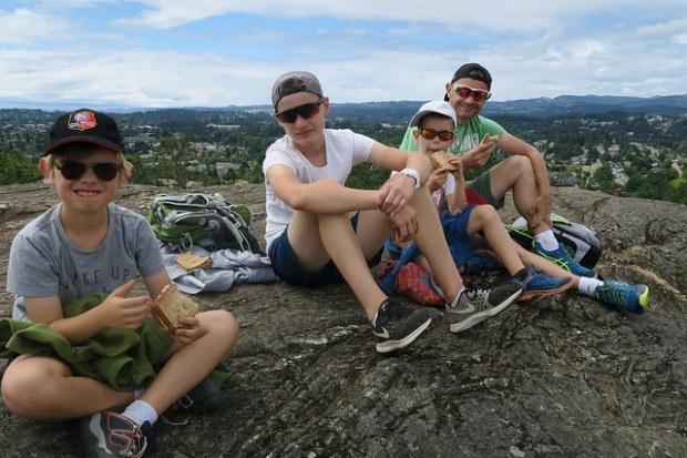 Les garçons assis pour pique-niquer en haut d'un mont