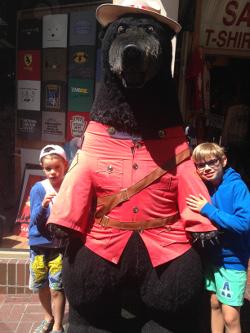 Merlin et Saik entourent une peluche géante d'un ours déguisé en ranger
