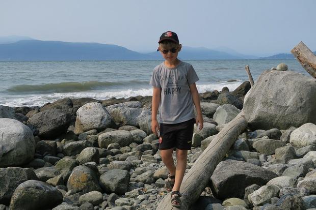 Saïj en équilibre sur un tronc d'arbre sur la plage
